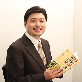本を持つ飯塚浩一